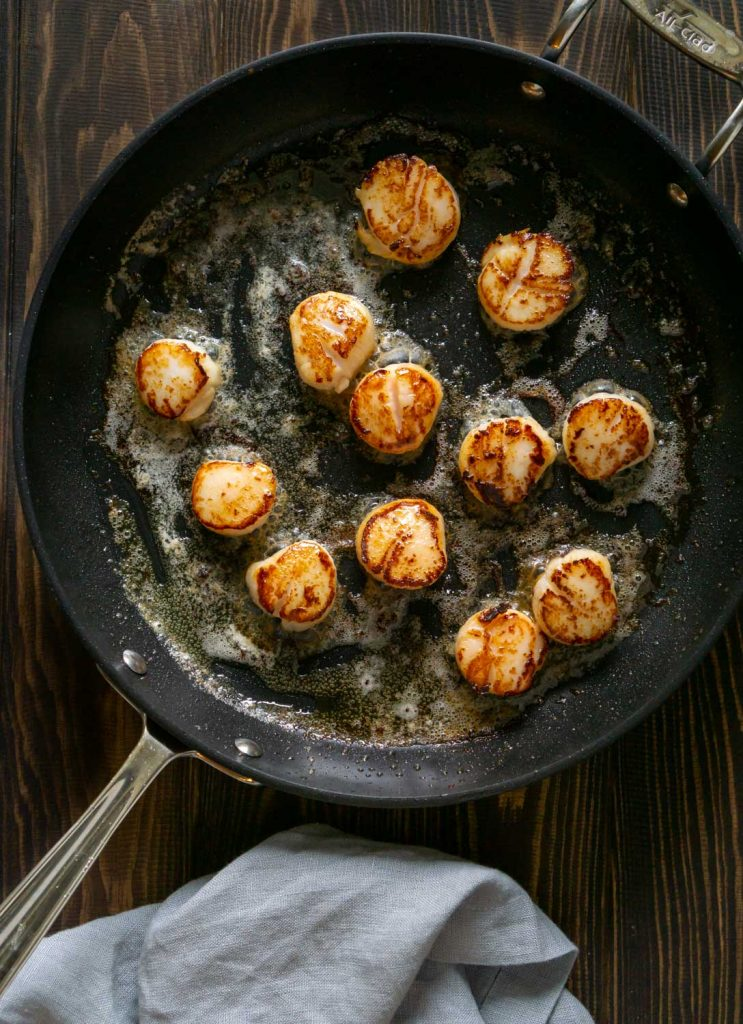 seared scallops in a pan and a grey napkin