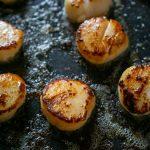 seared scallops in a black pan