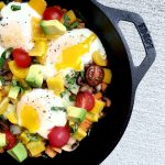 Overhead photo of veggies and eggs in a skillet