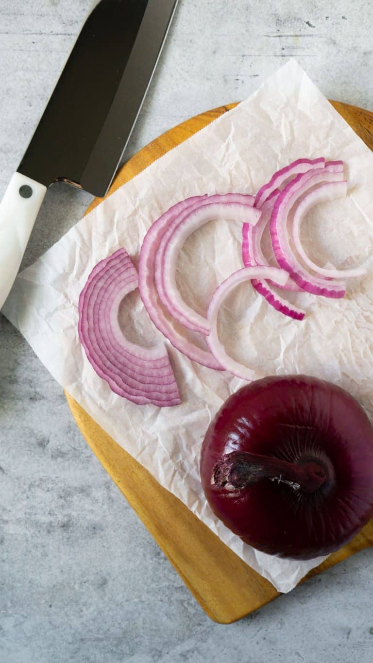 sliced onion on a cutting board with a knife