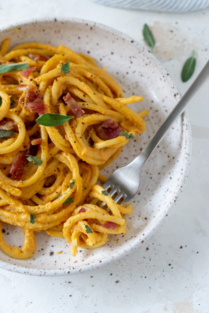 pumpkin pasta on a white plate with a silver fork