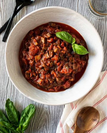 mushroom bolognese sauce in a large white bowl and fresh basil