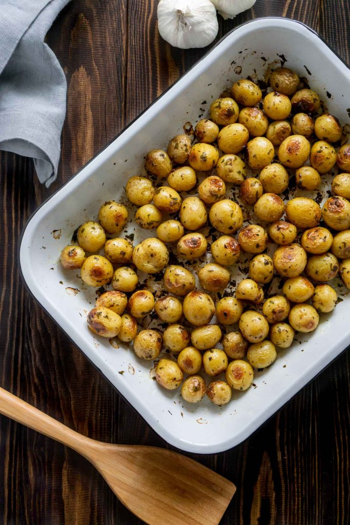 roasted mini potatoes in a white baking pan and garlic on the side