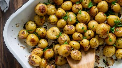 roasted mini potatoes in a white baking dish with a wooden spoon