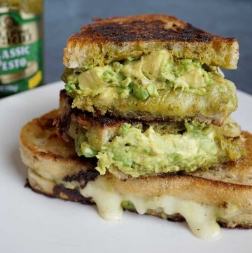 pesto grilled cheese cut in half and stacked with pesto jar