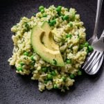 avocado risotto on a black plate with a silver fork and spoon