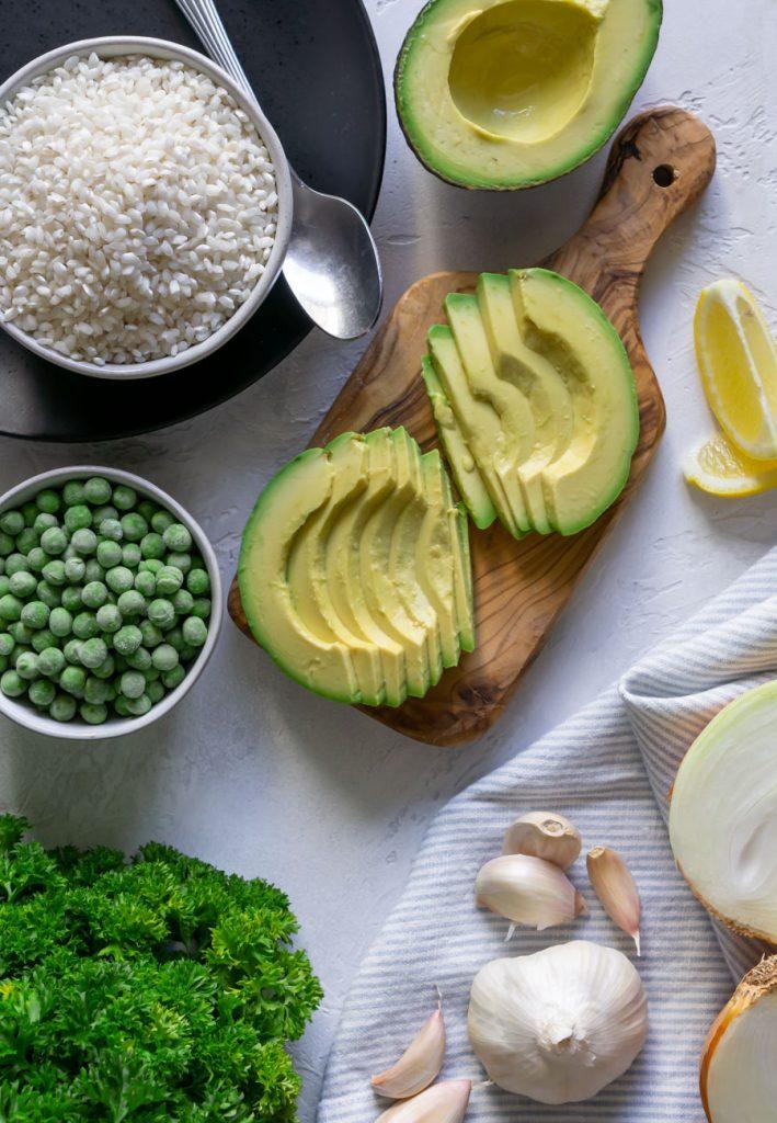 sliced avocados, a bowl of arborio rice, parsley, frozen peas, and garlic