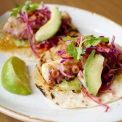 Octopus tacos on a white plate with a lime