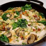 Chicken, spinach, mushrooms, and cream sauce in a cast iron pan