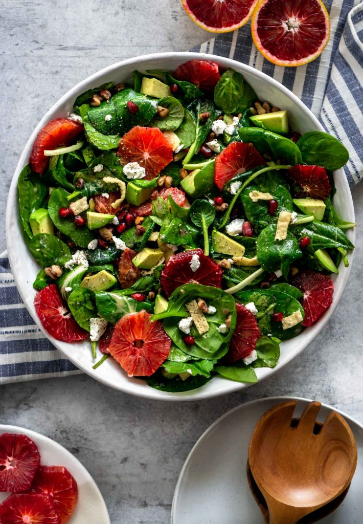 winter citrus green salad in a large bowl and sliced blood oranges off to the side
