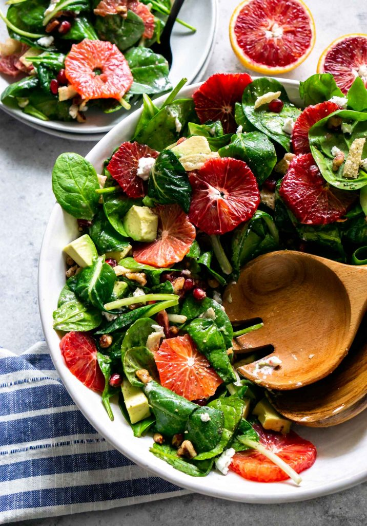 winter citrus green salad in a large white bowl with salad tossers