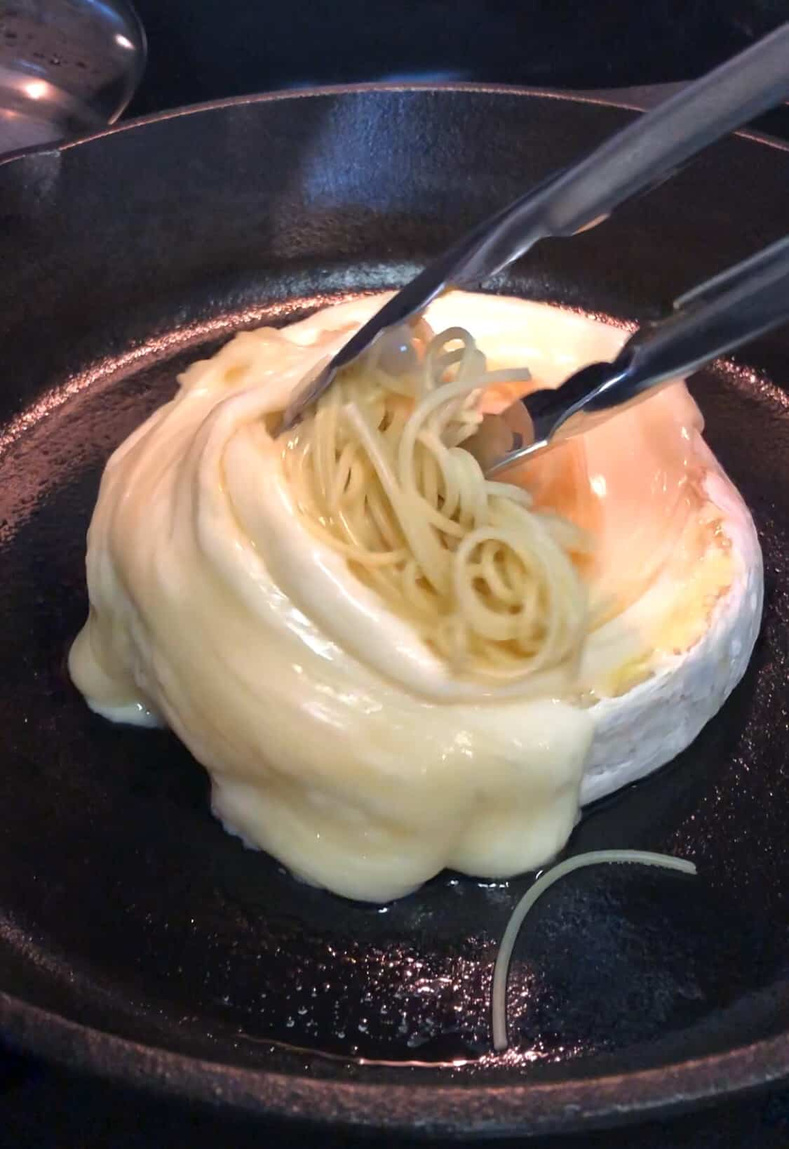 Tongs twirling spaghetti in brie cheese