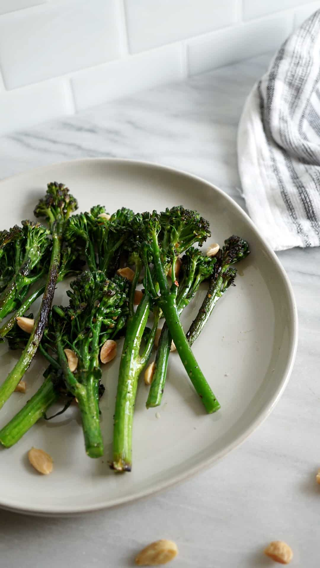Broccolini and marcona almonds on a white plate with a striped dish towel