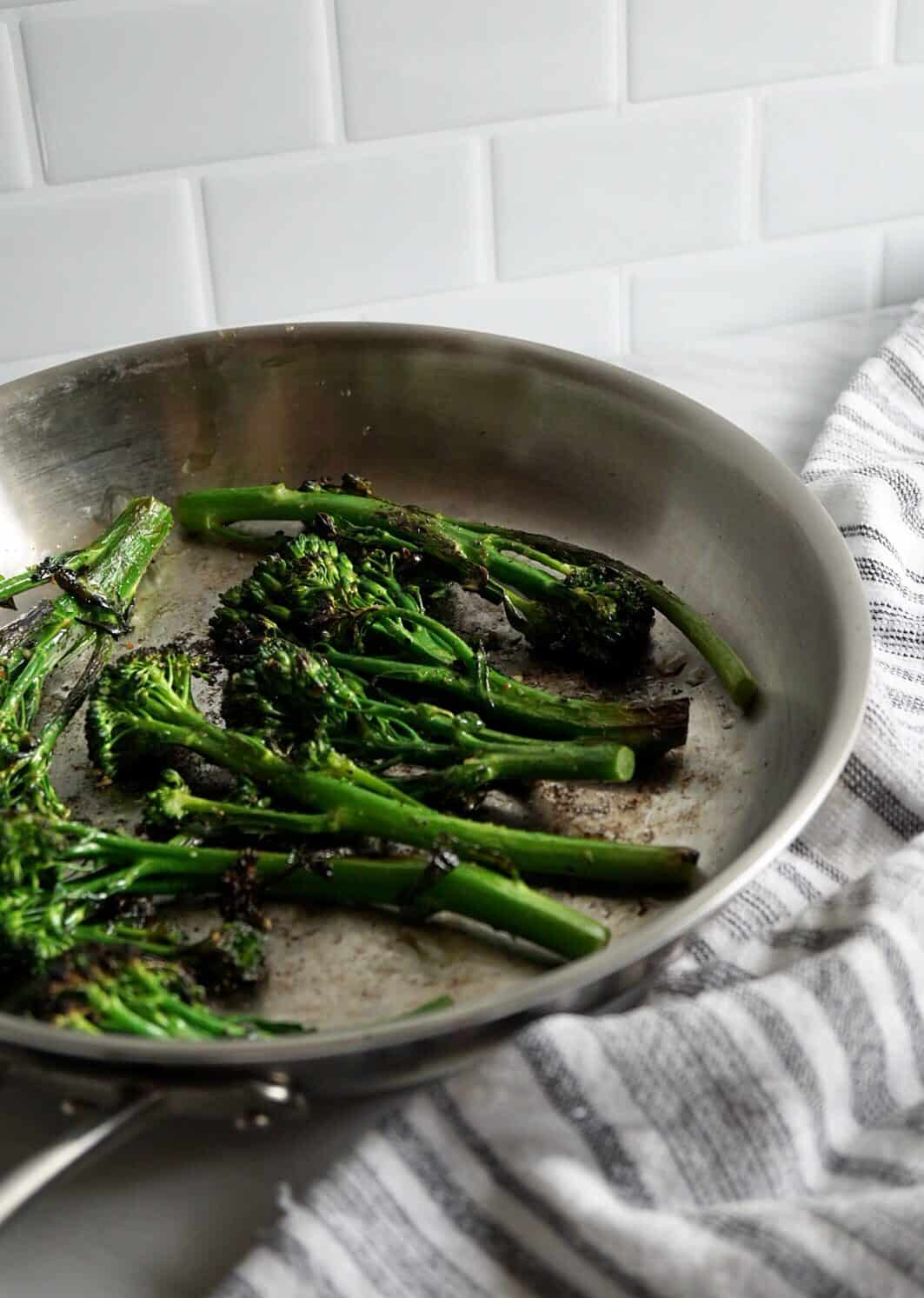 Broccolini in a silver skillet with a striped towel