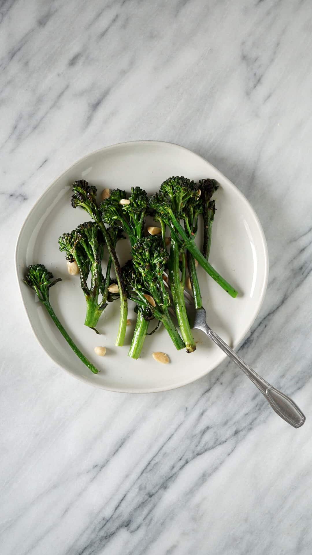 Broccolini on a white plate with a fork