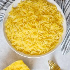 Spaghetti squash in a white bowl with two gold forks