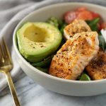 whole30 salmon bowl with gold fork and grey napkin