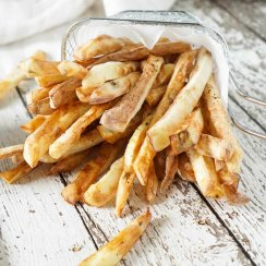 Air fryer french fries spilling out of a basket with ketchup
