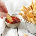 french fry dipped in ketchup and fries in a basket