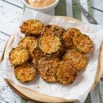 Zucchini chips on a plate with sauce