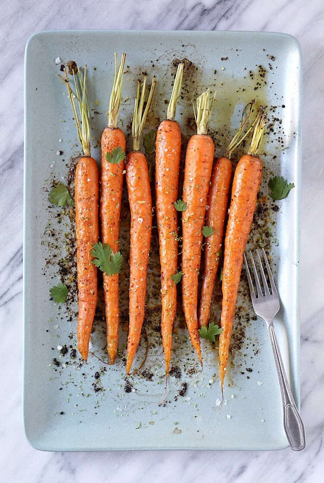 Chili lime roasted carrots on a blue platter