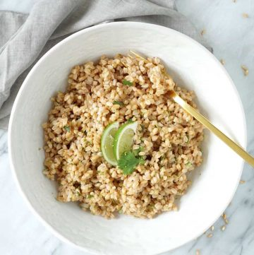 Cilantro lime farro in a white bowl with a gold fork