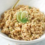 Cilantro lime farro in a white bowl with gold utensils