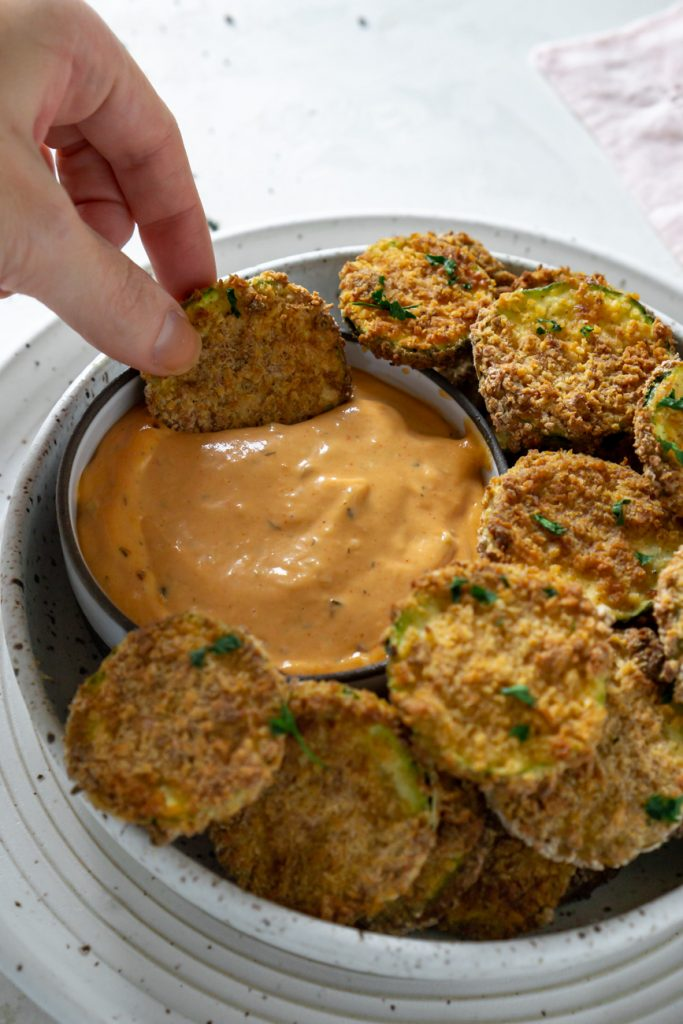 dipping zucchini chip in sauce