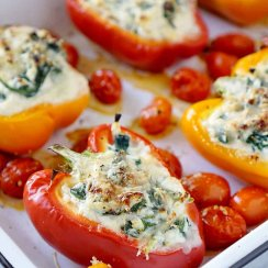 Stuffed peppers in a white pan with tomatoes