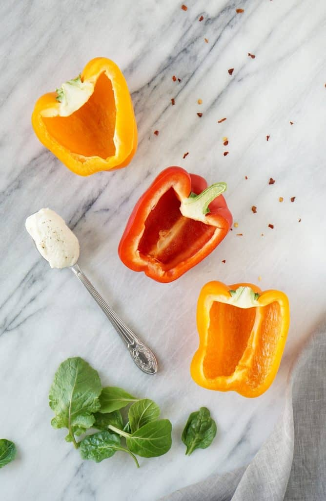 3 peppers on a marble slab with ricotta on a spoon