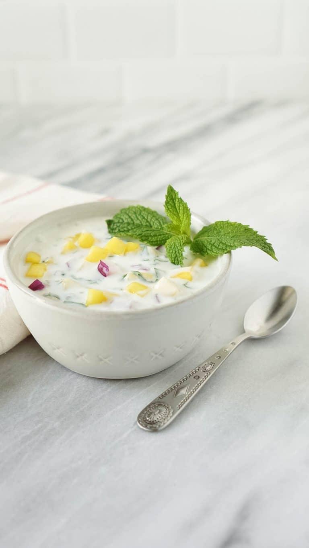 mango yogurt chutney in a small bowl with a spoon