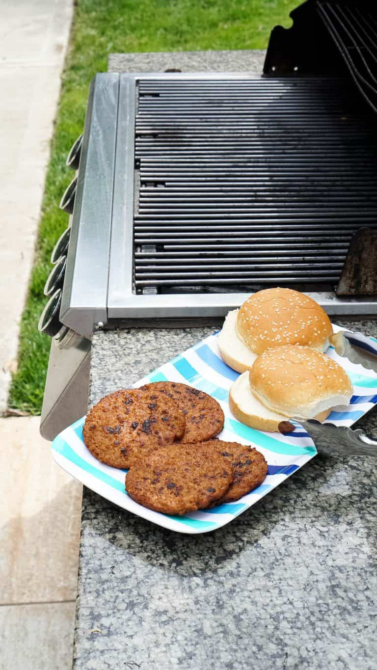 veggie burgers and buns next to a grill