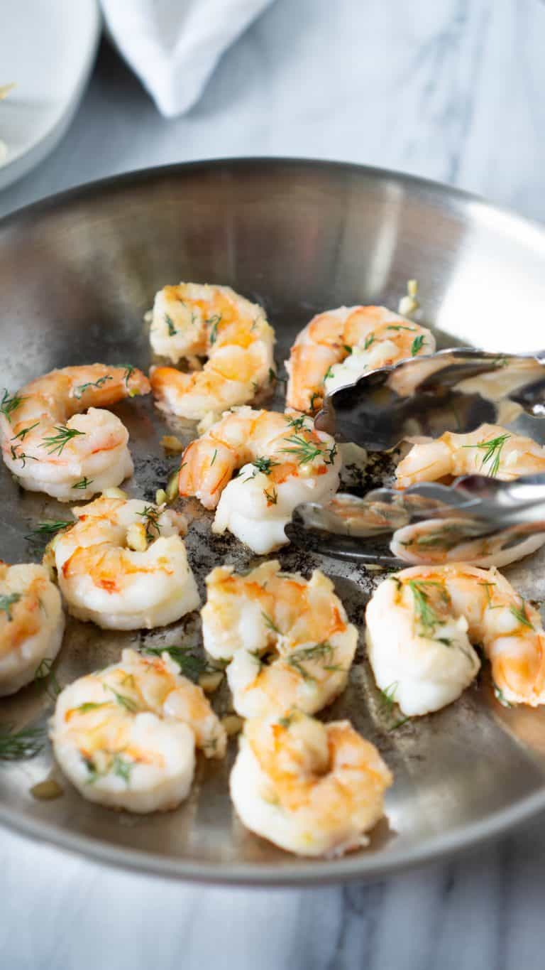 garlic butter shrimp in a pan with tongs