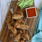 Overhead view of crispy air-fryer chicken wings with celery and wing sauce.