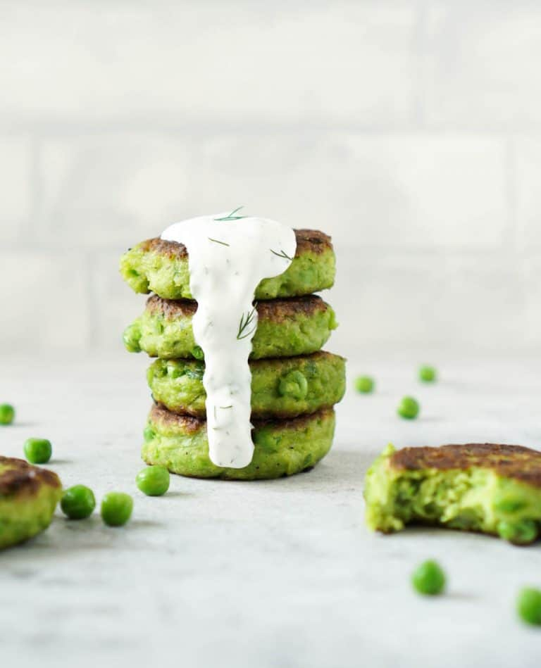 4 pea fritters stacked with dill yogurt sauce