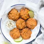 salmon cakes on a white plate with limes