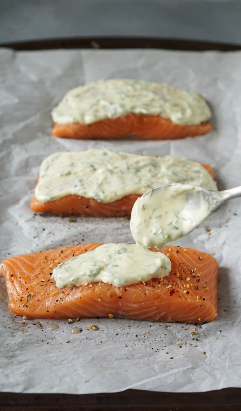 a spoon spreading herb mayonnaise on raw salmon