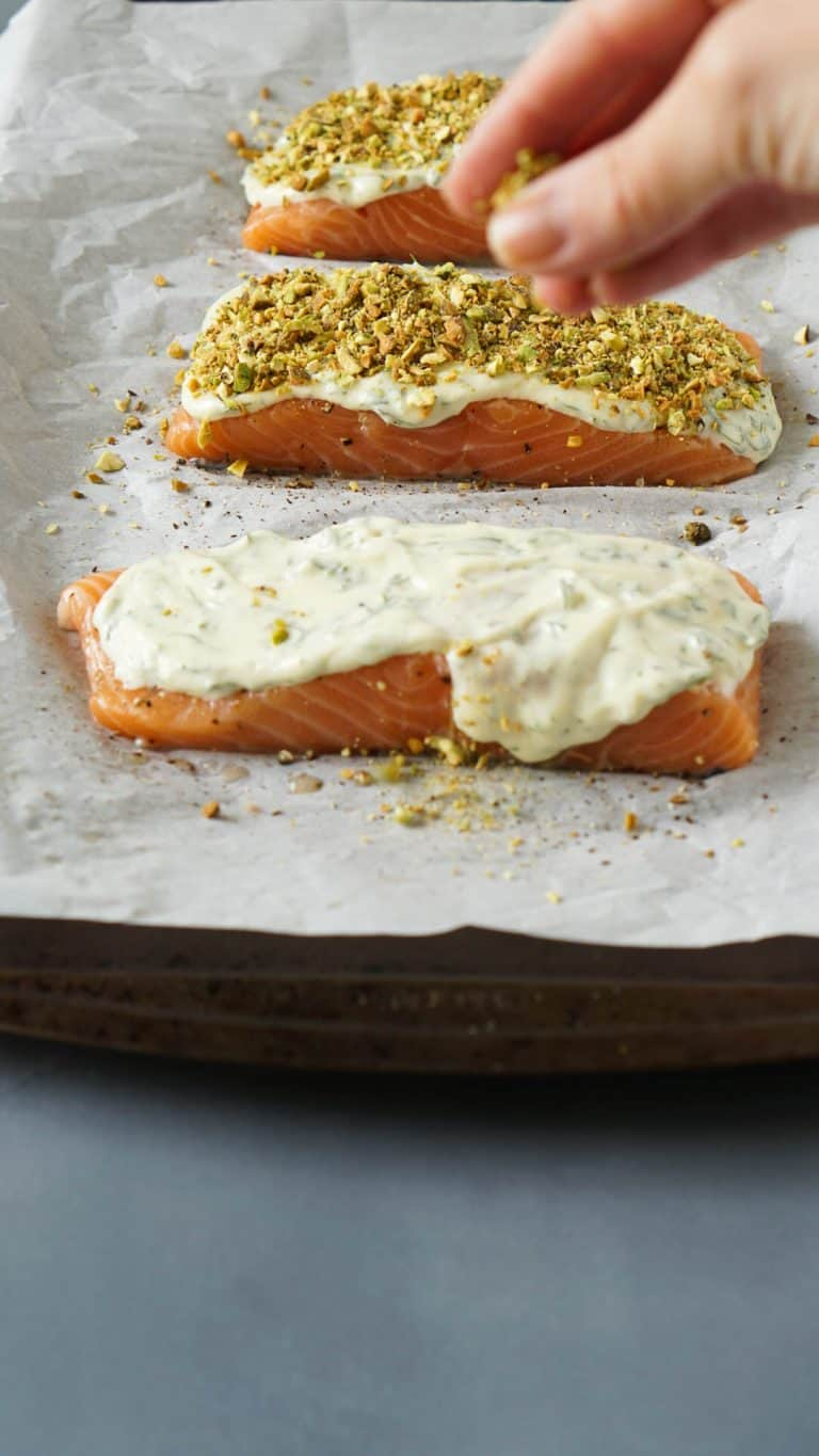 a hand sprinkling crushed pistachios over salmon