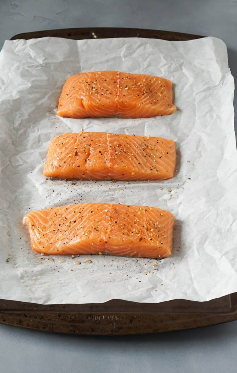 3 filets of raw salmon on a baking sheet