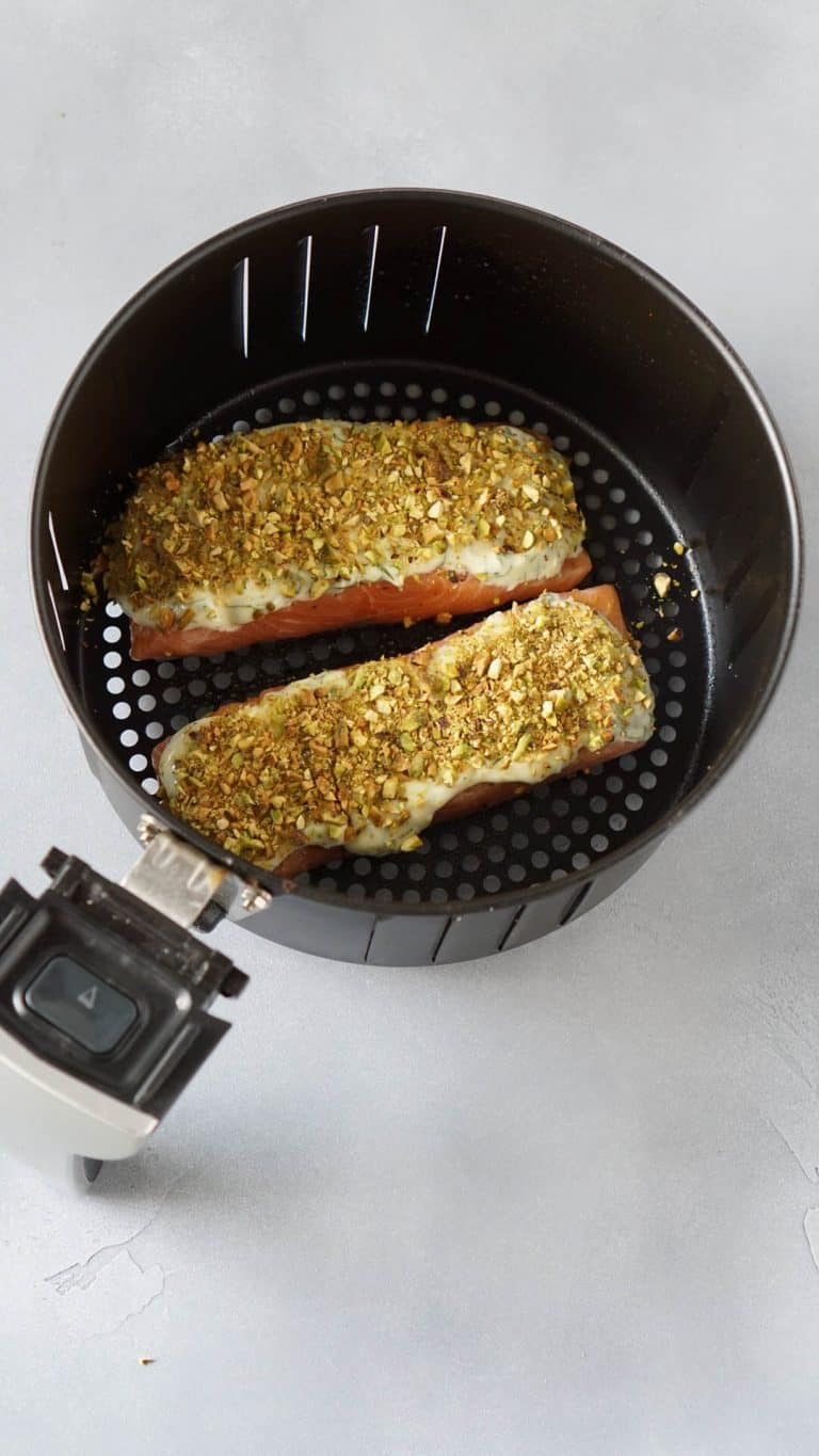 two salmon filets with pistachios in an air fryer basket