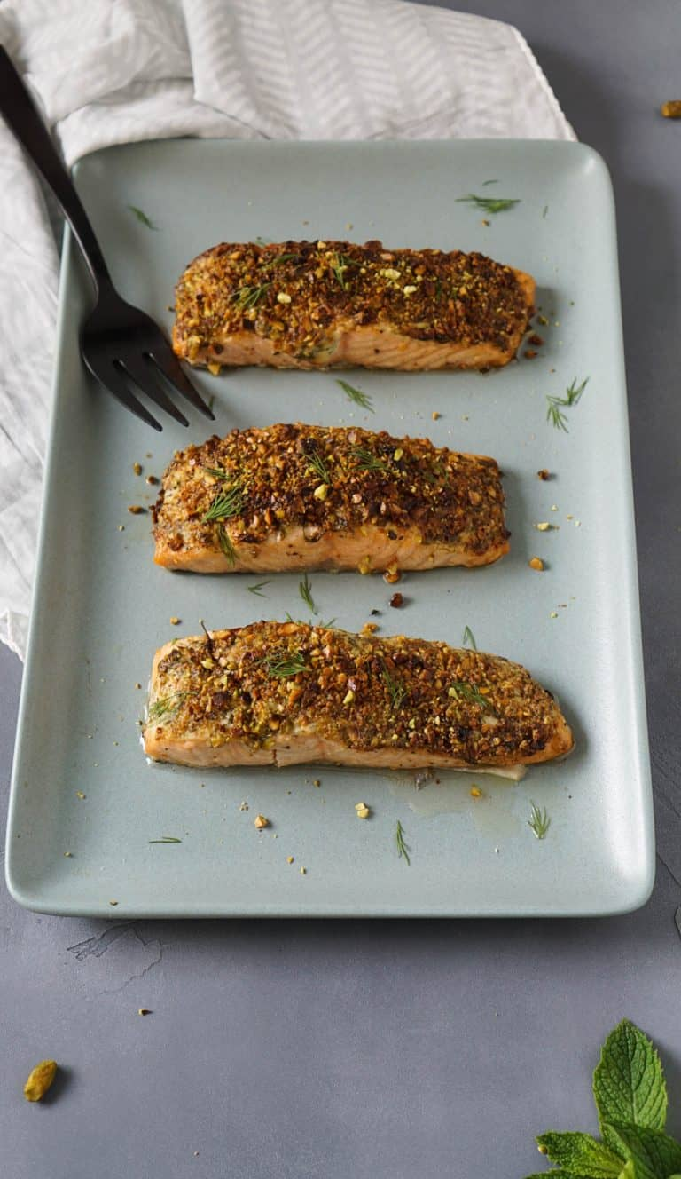 pistachio crusted air fryer salmon on a blue serving tray with a black serving fork