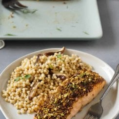 air fryer salmon on a white plate with couscous and a fork