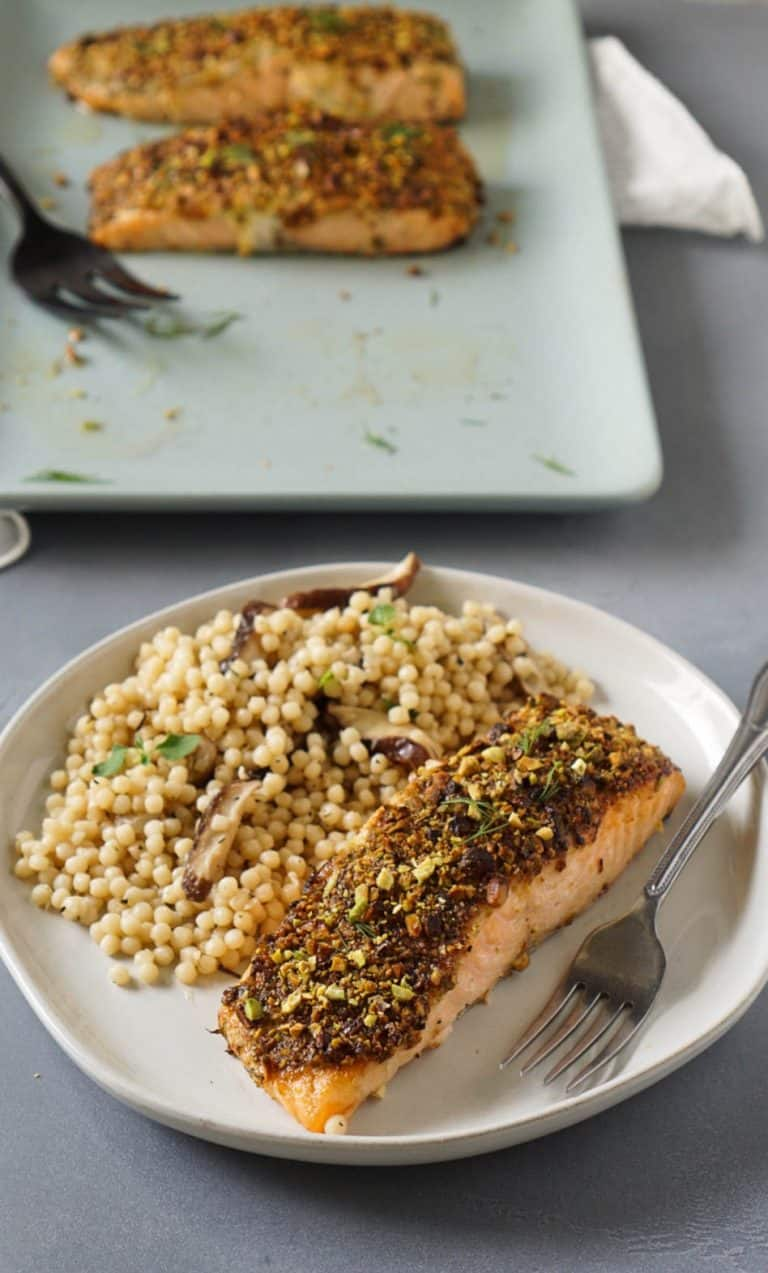 pistachio crusted air fryer salmon on a white plate with couscous and a fork