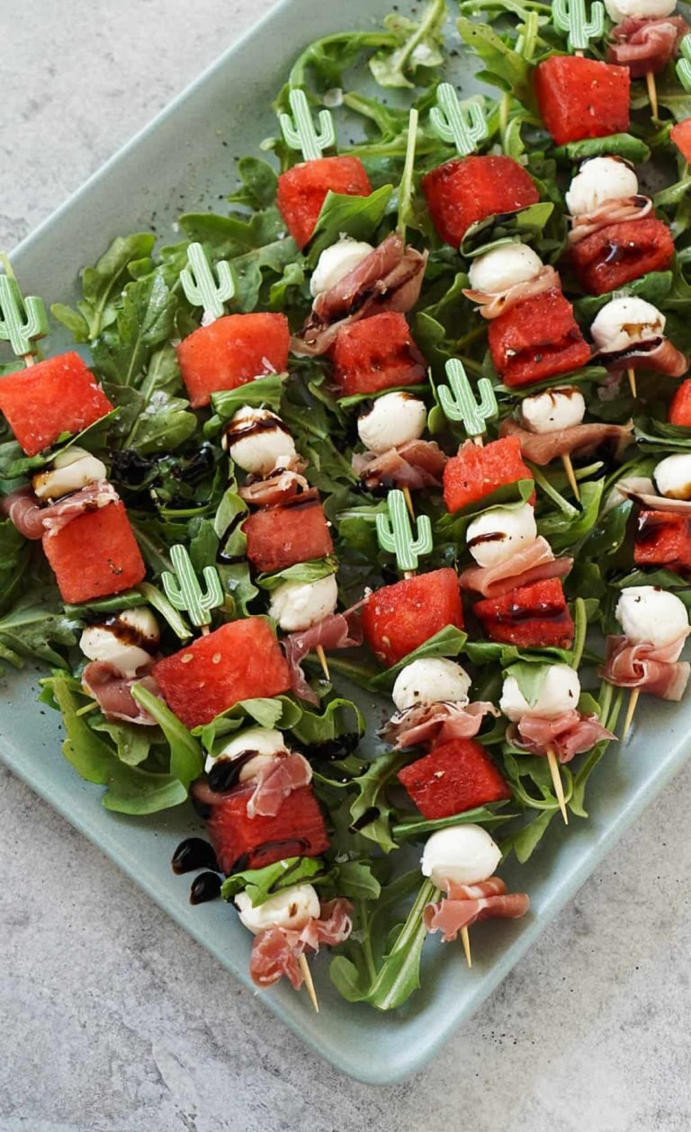 watermelon caprese skewers on a blue platter with arugula