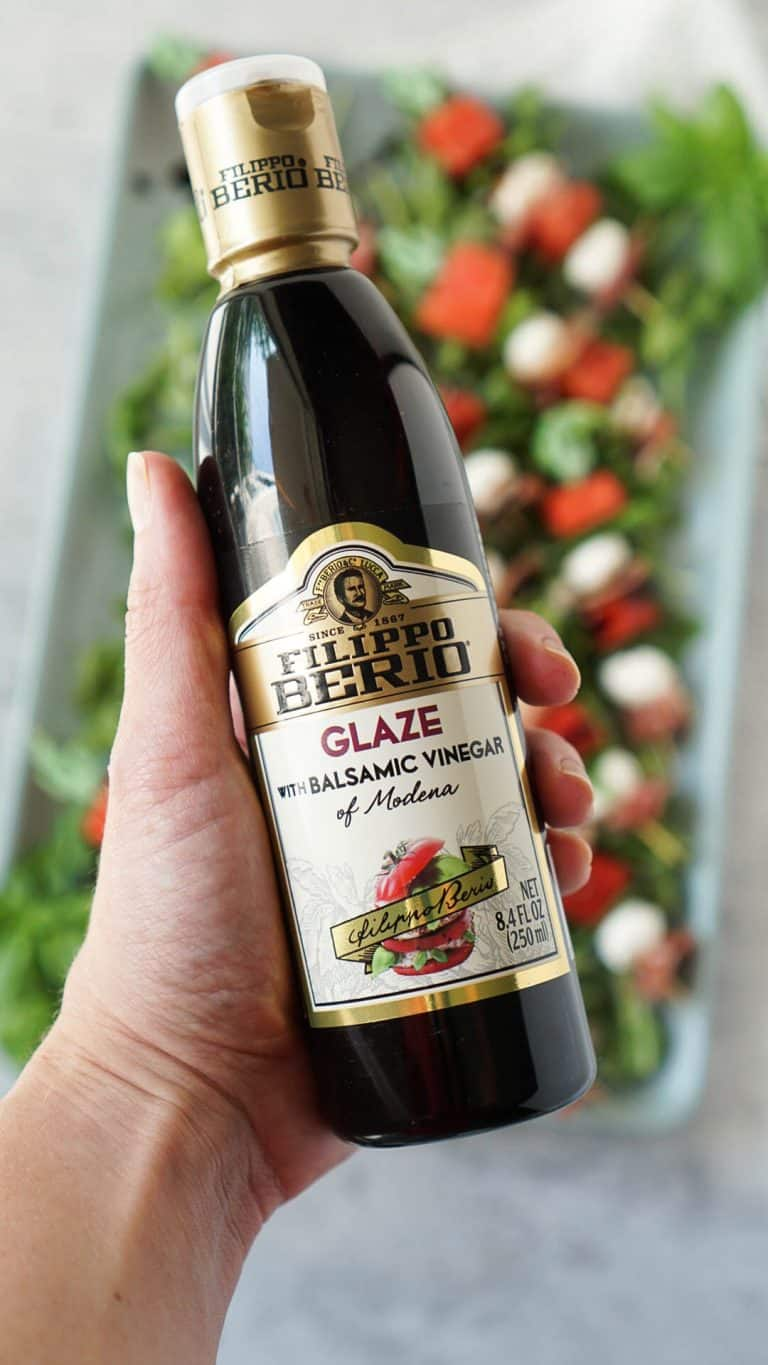 hand holding a bottle of filippo berio balsamic glaze