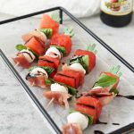caprese skewers on a black tray with filippo berio balsamic glaze
