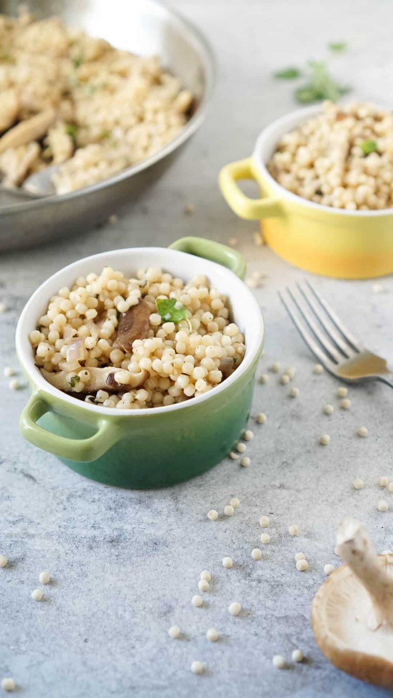 israeli couscous recipe in two colored bowls with a fork