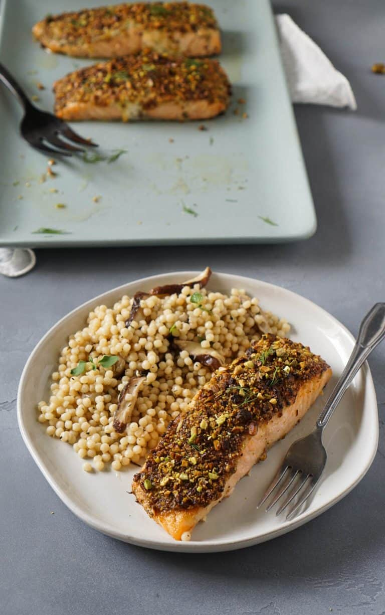salmon on a white plate with israeli couscous