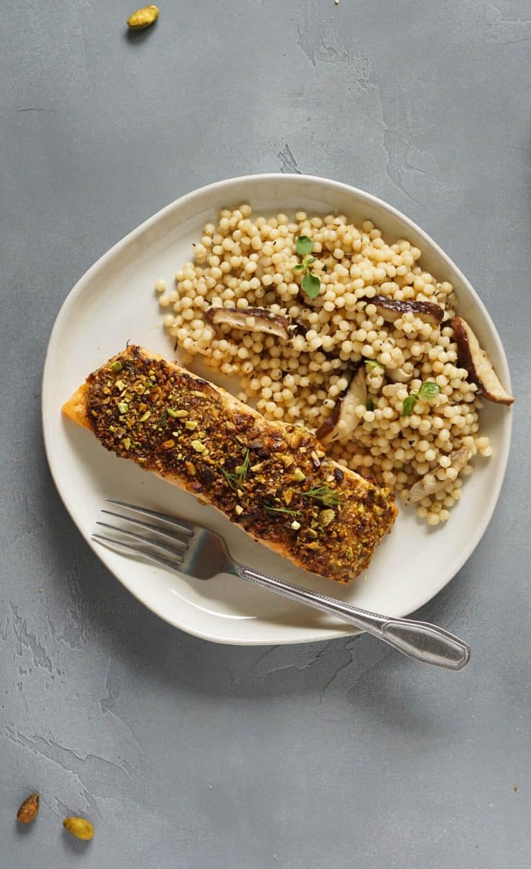 salmon on a white plate with israeli couscous and a fork