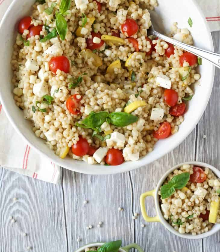 couscous salad in 2 small bowls and 1 large bowl